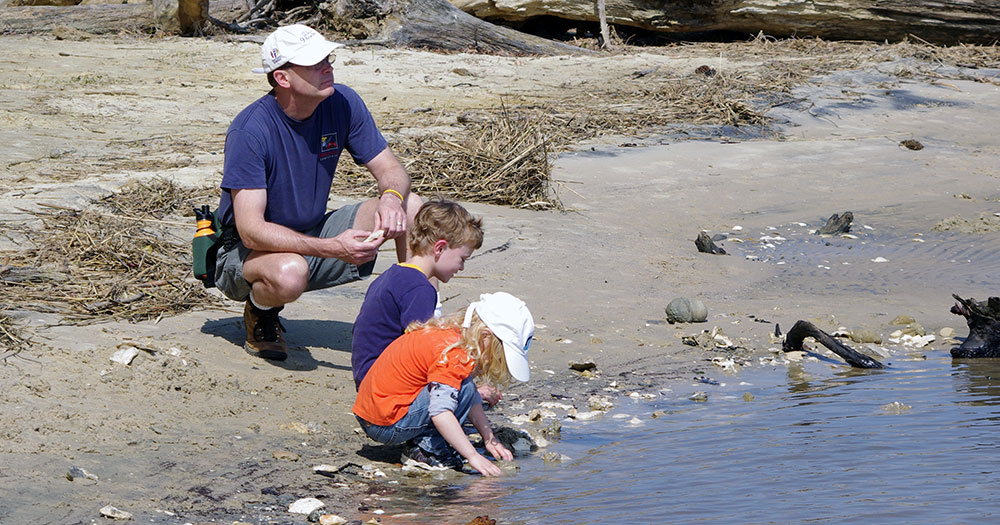 Dad with kids at estuary bank